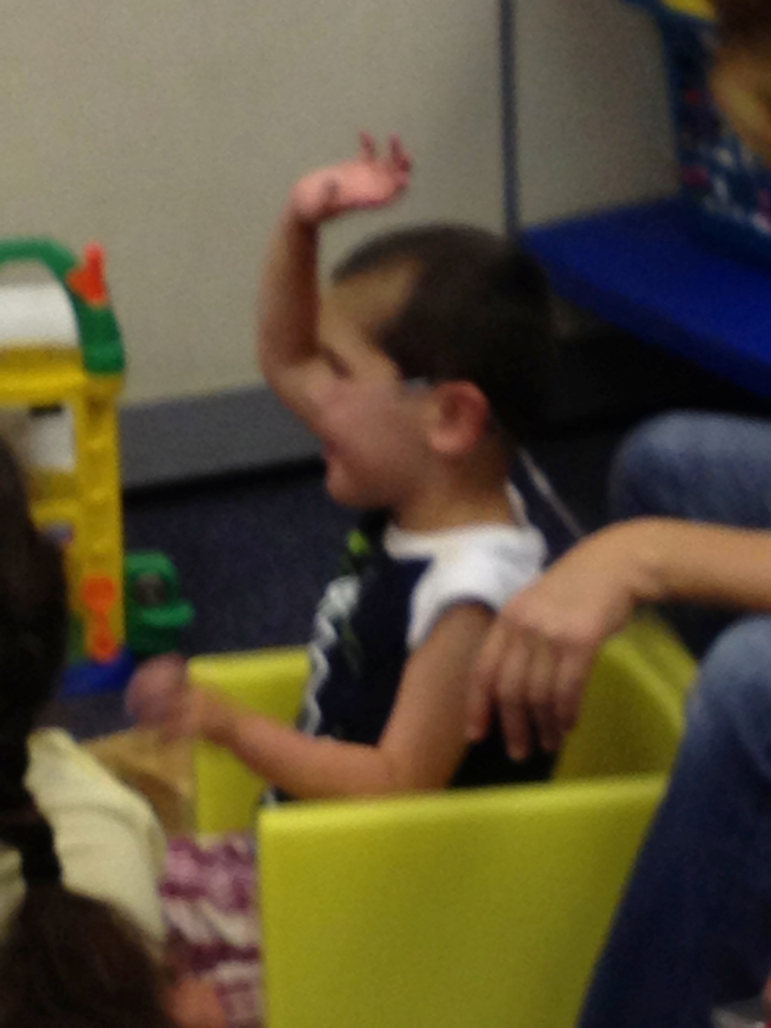 Rudy politely raising his hand and waiting his turn to lead a song during circle time!